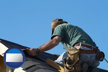 a roofing contractor installing asphalt roof shingles - with Kansas icon