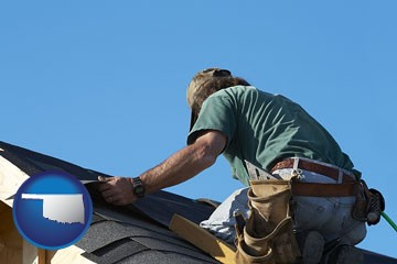 a roofing contractor installing asphalt roof shingles - with Oklahoma icon