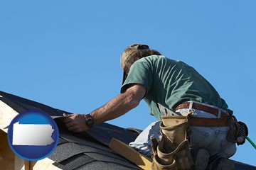 a roofing contractor installing asphalt roof shingles - with Pennsylvania icon