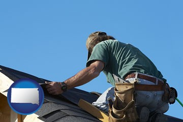a roofing contractor installing asphalt roof shingles - with South Dakota icon