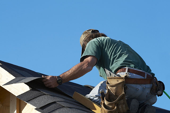 a roofing contractor installing asphalt roof shingles